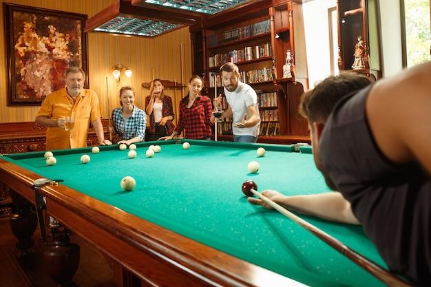 Hombres y mujeres sonrientes jovenes que juegan al billar en la oficina o en casa después del trabajo. compañeros de trabajo que participan en actividades recreativas