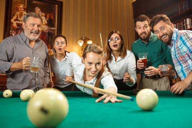 Hombres y mujeres sonrientes jovenes que juegan al billar en la oficina o en casa después del trabajo.