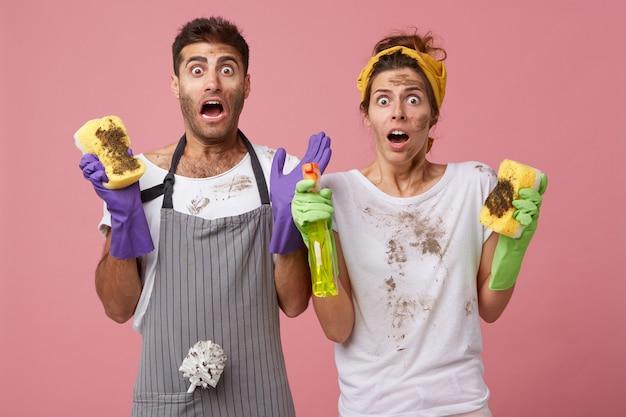Hombres y mujeres sorprendidos haciendo quehaceres con ropa casual mirando con sorpresa la nevera muy sucia sin saber cómo limpiarla. pareja familiar en pánico asustando de las tareas del hogar y ordenando