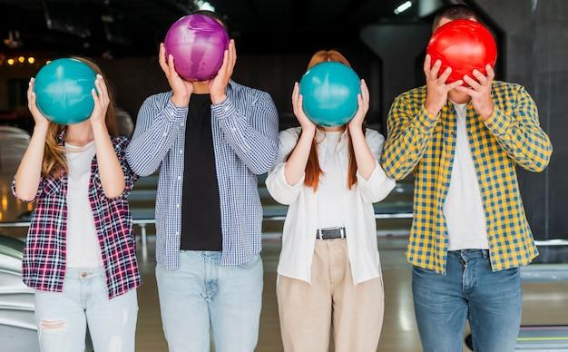Hombres y mujeres sosteniendo una bola de boliche en la cabeza