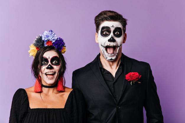 Hombres y mujeres traviesos alegres en ropa negra con detalles en rojo gritan de asombro, posando con maquillaje de halloween para el retrato.