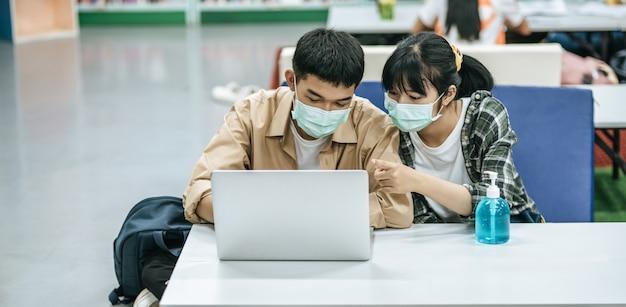 Hombres y mujeres usan máscaras y usan una computadora portátil para buscar libros en la biblioteca.