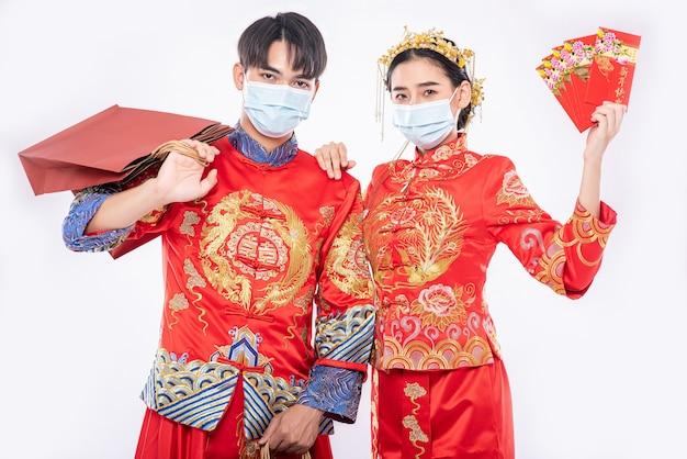 Hombres y mujeres vistiendo qipao y con máscaras llevando bolsas de papel para comprar con sobre rojo