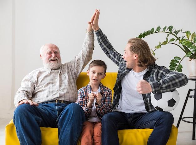 Hombres multigeneracionales exultando al equipo de fútbol de la victoria en casa.