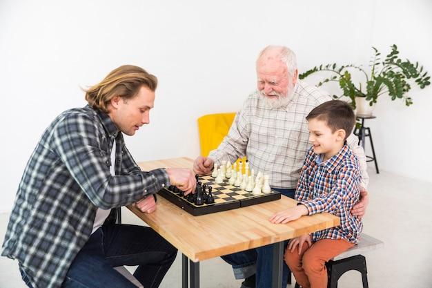 Hombres multigeneracionales jugando al ajedrez.