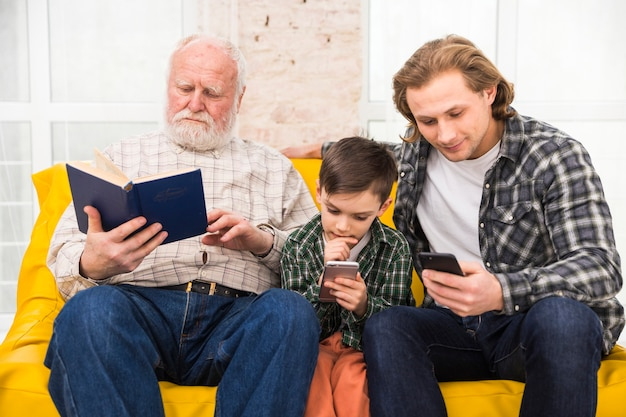 Hombres multigeneracionales leyendo libros y teléfonos inteligentes.