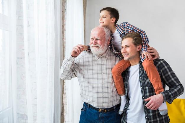 Hombres multigeneracionales de pie y con sonrisa apartando la mirada.