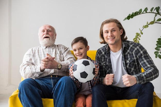 Hombres multigeneracionales viendo fútbol en casa.