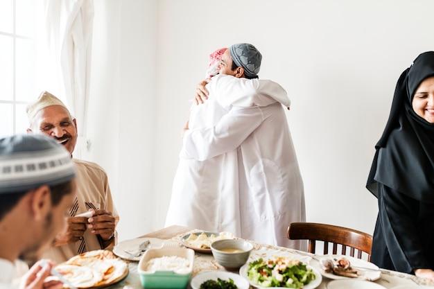 Hombres musulmanes abrazándose en el almuerzo