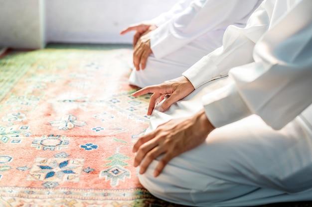 Hombres musulmanes rezando en postura de tashahhud