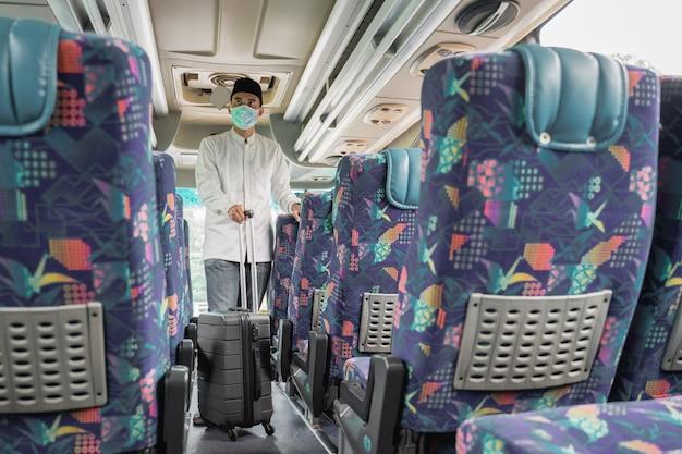 Hombres musulmanes viajan en autobús público durante la pandemia con máscara