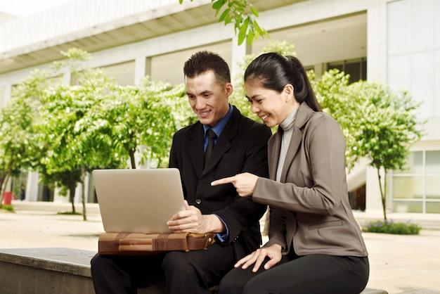 Hombres de negocios asiáticos jovenes que discuten el trabajo con el ordenador portátil