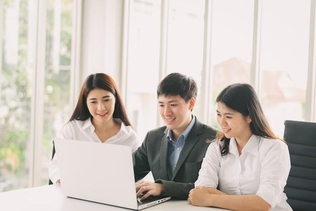 Hombres de negocios asiáticos jovenes que trabajan con el ordenador portátil