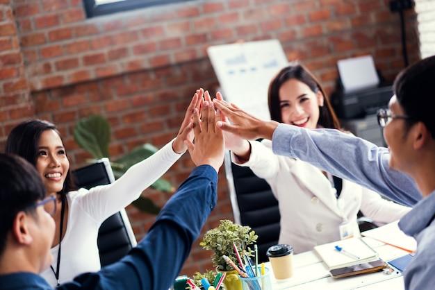 Hombres de negocios asiáticos que se colocan en oficina y que dan el alto cinco durante el teambuilding.