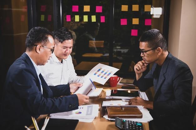 Hombres de negocios asiáticos que discuten el trabajo que se sienta en sala de conferencias de la oficina en la escena de la noche