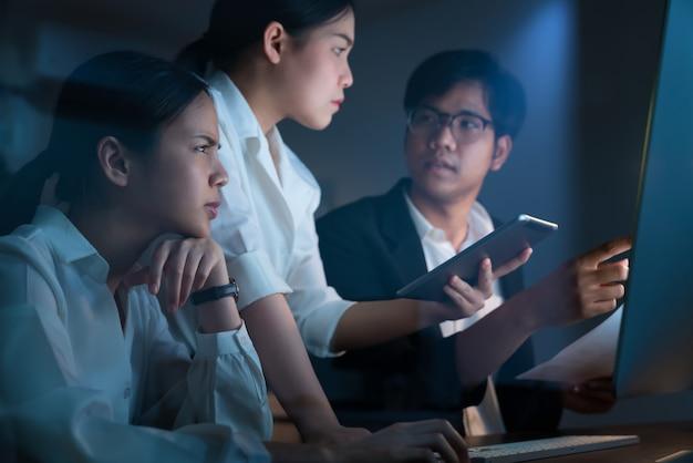 Hombres de negocios asiáticos que trabajan duro tarde juntos y planean con la computadora en la oficina por la noche, el concepto de trabajo en equipo de logro de éxito