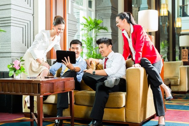 Hombres de negocios chinos asiáticos reunidos en el vestíbulo del hotel