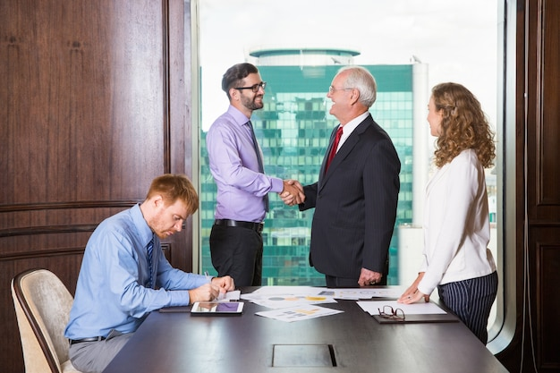 Hombres de negocios dándose la mano mientras otro esta escribiendo