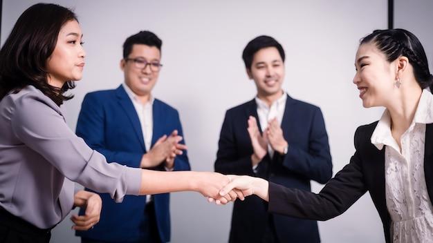 Hombres de negocios dándose la mano, entre la reunión en la sala de seminario