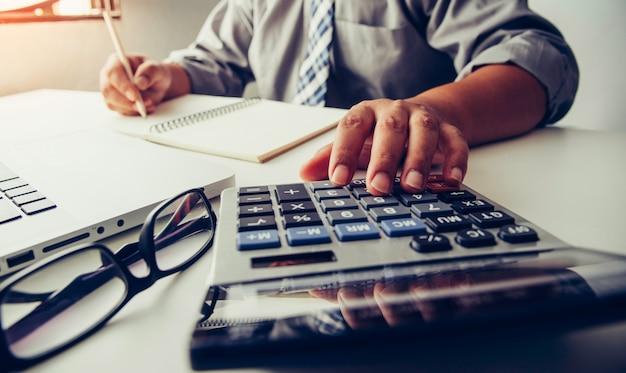 Los hombres de negocios están usando una calculadora para calcular los ingresos del negocio.
