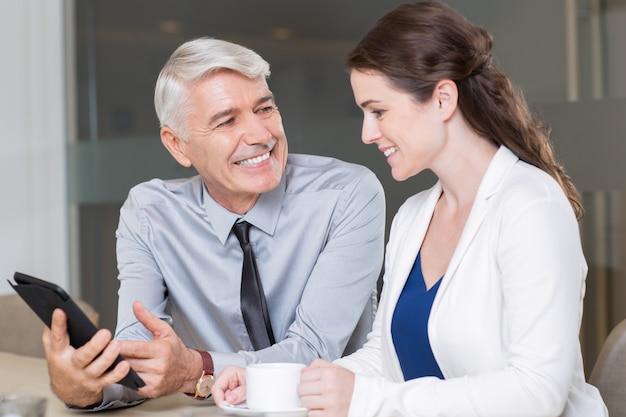 Hombres de negocios felices que discuten proyecto en el café