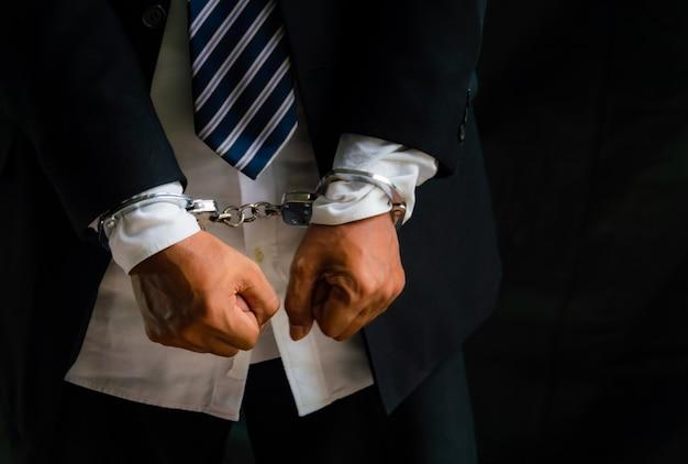 Los hombres de negocios fueron arrestados y esposados porque hacen negocios ilegales.