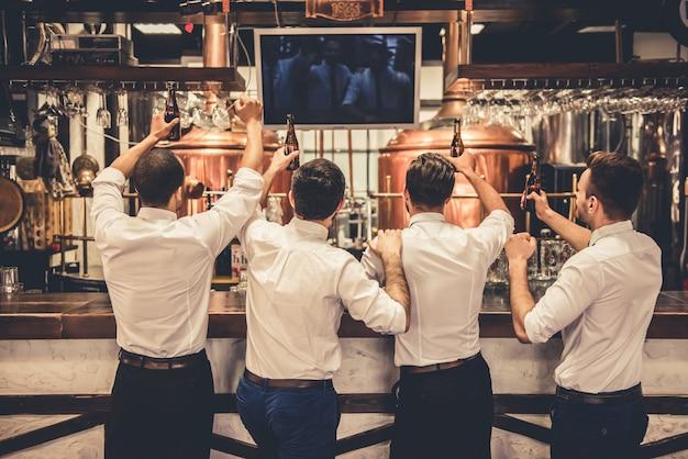 Hombres de negocios guapos están bebiendo cerveza.