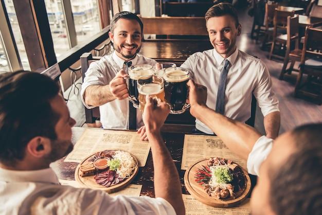 Hombres de negocios guapos son tintinear jarras de cerveza.