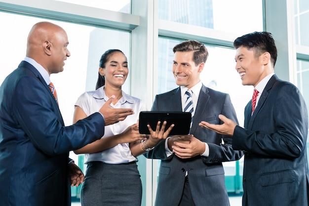 Hombres de negocios informales con mesa de ordenador discutiendo