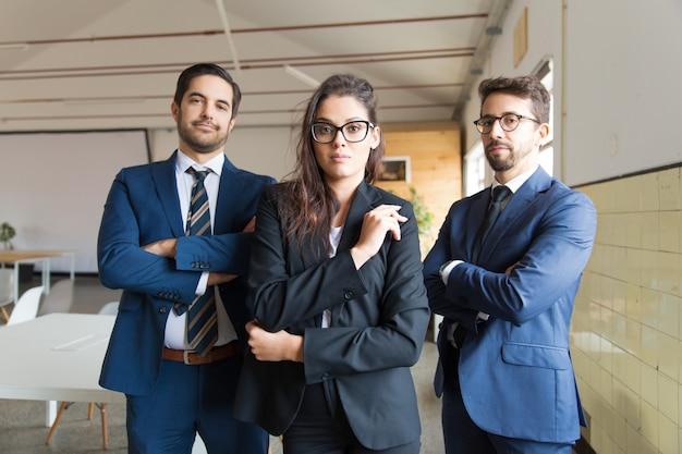 Hombres de negocios jovenes confiados que presentan con los brazos cruzados