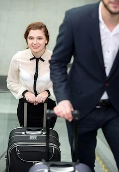 Hombres de negocios jovenes con una maleta en aeropuerto.