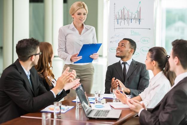 Hombres de negocios jovenes en los trajes que se sientan en la sala de reunión.