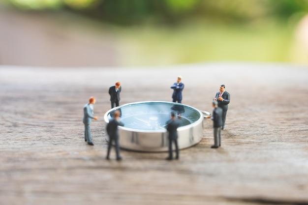 Los hombres de negocios en miniatura analizan la posición en el compás como estrategia de fondo