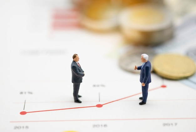 Hombres de negocios en miniatura discuten en línea gráfico de crecimiento empresarial.