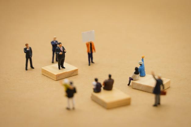 Hombres de negocios en miniatura personas de pie declaración de política para luchar