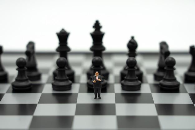 Hombres de negocios en miniatura de personas de pie en un tablero de ajedrez con una pieza de ajedrez