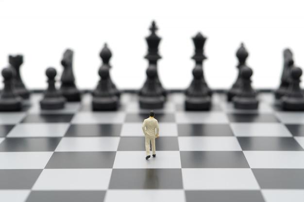 Hombres de negocios en miniatura de pie sobre un tablero de ajedrez con una pieza de ajedrez en la parte posterior.