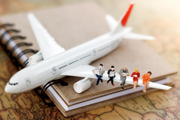 Hombres de negocios miniatura que se sientan en el aeroplano con el mapa del mundo usando como concepto del viaje y del negocio.
