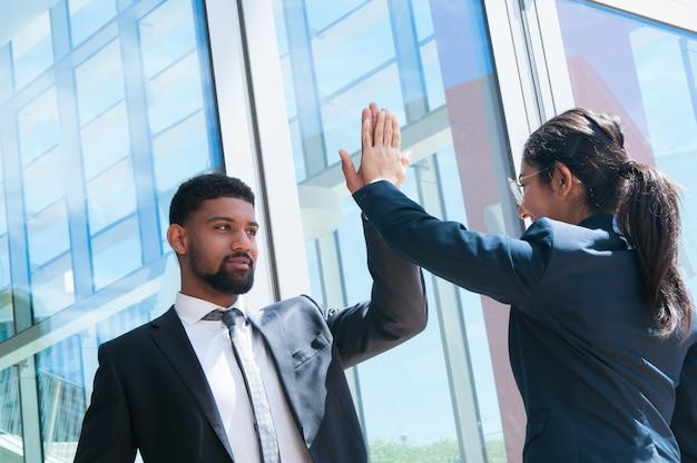 Hombres de negocios positivos alto fiving al aire libre