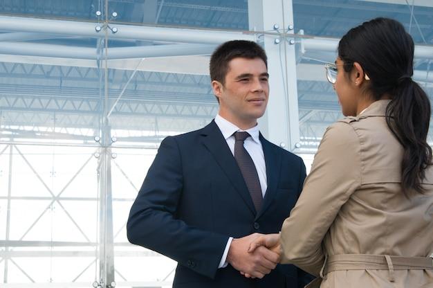 Hombres de negocios positivos que se encuentran y que sacuden las manos al aire libre