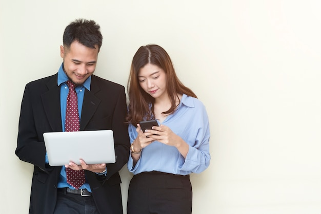 Hombres de negocios que se colocan en la pared y que trabajan con el móvil y la computadora portátil con la sonrisa.
