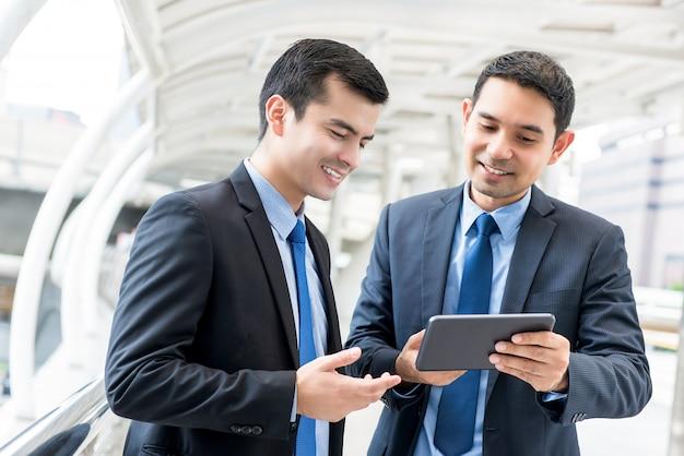Hombres de negocios que discuten proyecto en la tableta digital