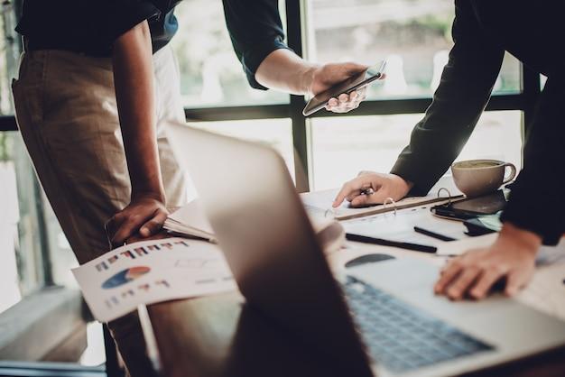 Hombres de negocios que discuten las tablas y gráficos que muestran los resultados de su éxito t