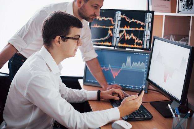 Hombres de negocios que negocian acciones en línea. corredores de bolsa que miran gráficos, índices y números en múltiples pantallas de computadora. colegas en discusión en la oficina de comerciantes. concepto de éxito empresarial.