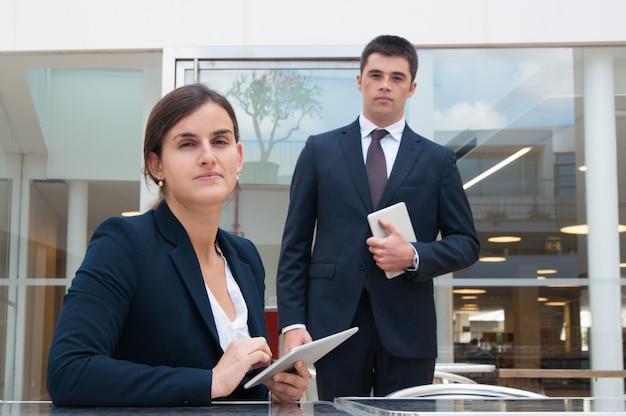 Hombres de negocios que presentan en la cámara y que sostienen las tabletas