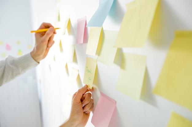 Los hombres de negocios que se reúnen en el poste de la oficina colorearon etiquetas de las notas en el tablero concepto de lluvia de ideas.