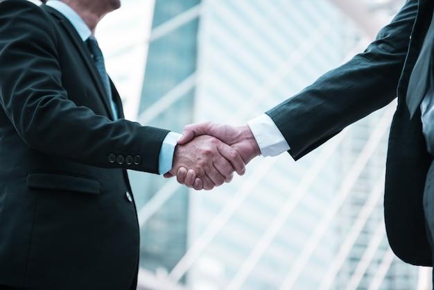 Hombres de negocios que sacuden las manos, concepto del saludo que saluda, fondo moderno de la ciudad.