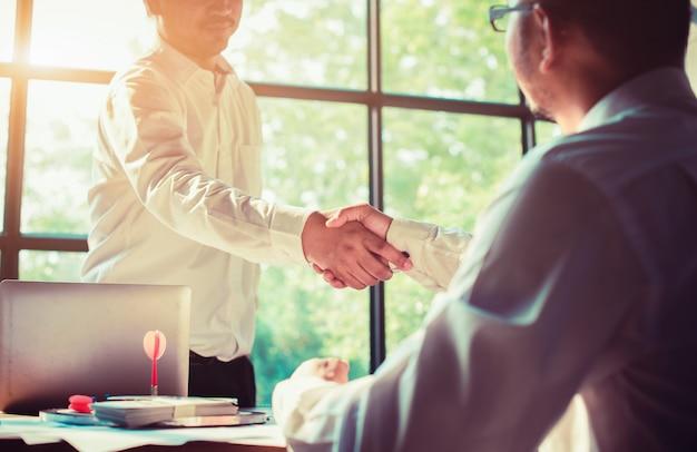 Hombres de negocios que sacuden las manos en la oficina.