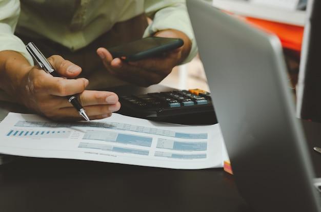 Los hombres de negocios que sostienen la pluma y el teléfono inteligente con informes de documentos comerciales financieros y una computadora portátil en el escritorio.