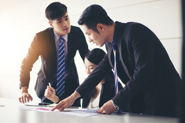 Los hombres de negocios que trabajan y apuntan en el diagrama del diagrama financiero y los documentos de análisis en la mesa de la oficina